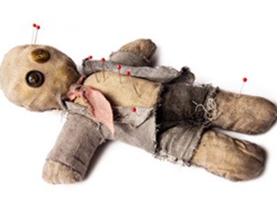 voodoo doll laying on white